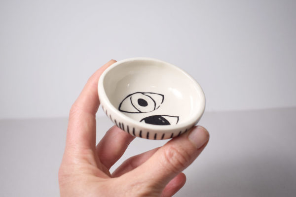 A hand holding a decorated ceramic bowl
